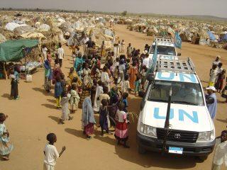 Véhicules des nations unies entourés d'une foule de personnes dans un camp d'aide dans une zone aride