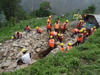 ouvriers en gilet orange regroupés pour construire une route dans une zone accidentées