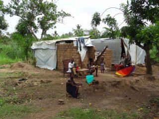 Famille devant leur maison en construction dans une zone végétale