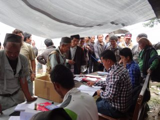Personnes réunis autour d'une table remplie de papiers sous une tente